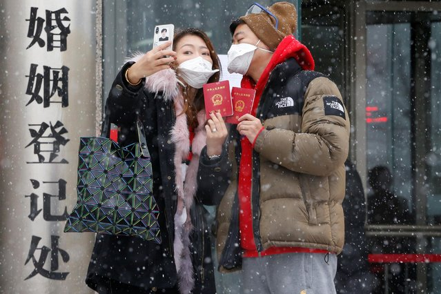 A couple poses with face masks and marriage certificates outside a registry of marriage on Valentine's Day in Beijing, February 14, 2020. (Photo by Reuters/China Daily)