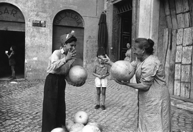 An elderly woman and a boy using hand signs to bargain for canteloupe melons, Italy, 1st November 1947