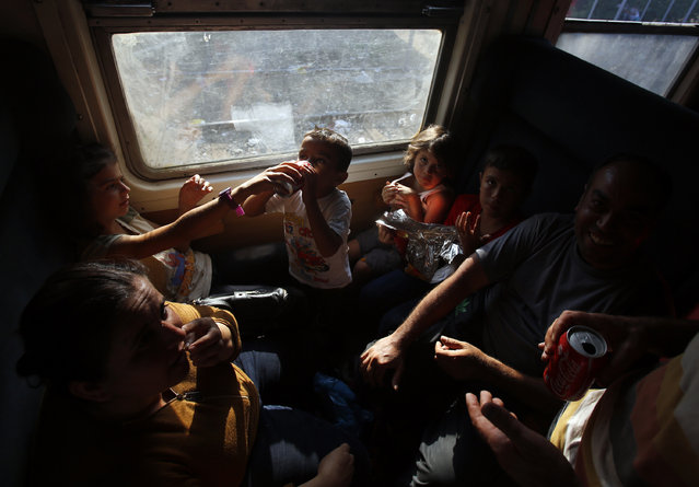 Migrants travel on train taking them towards Serbia, near the southern Macedonian town of Demir Kapija, Wednesday, August 19, 2015. Record numbers of migrants from countries like Syria, Iraq and Afghanistan uses the so-called Balkan route that passes trough Macedonia. (Photo by Darko Vojinovic/AP Photo)