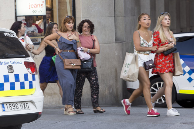 Shocked pedestrians leave the area after a van ploughed into the crowd, killing 13 persons and injuring over 50 on the Rambla in Barcelona on August 17, 2017. (Photo by Anadolu Agency/Getty Images)