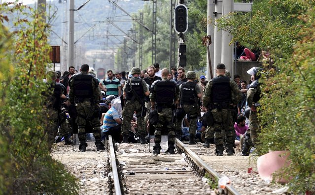 Macedonian special policemen guard the border as more than a thousand immigrants wait at the border line of Macedonia and Greece to enter Macedonia near the Gevgelija railway station August 21, 2015. Macedonian police drove back crowds of migrants and refugees trying to enter from Greece on Friday after a night spent stranded in no-man's land by an emergency decree effectively sealing the Macedonian frontier. (Photo by Ognen Teofilovski/Reuters)