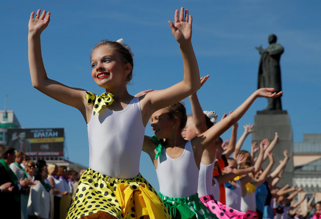 Young girls perform in front of the monument to Soviet state founder Vladimir Lenin during the City Day celebrations in Yekaterinburg, Russia on August 19, 2017. (Photo by Maxim Shemetov/Reuters)