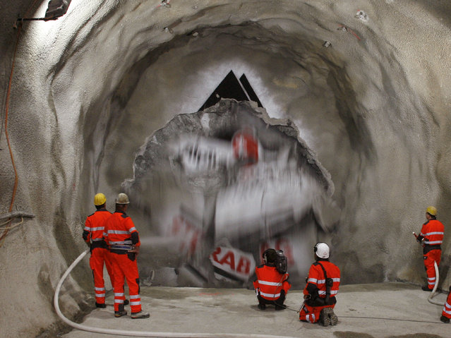 Miners stand in front as the drill machine 'Gaby' breaks through the rock at the section Erstfeld-Amsteg at the construction site of the NEAT Gotthard Base Tunnel June 16, 2009. (Photo by Arnd Wiegmann/Reuters)
