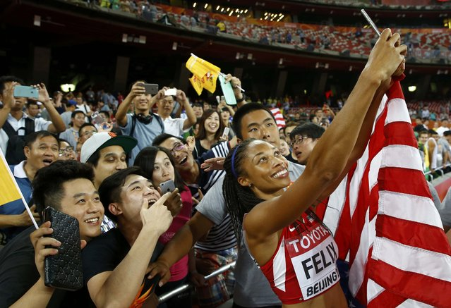 Allyson Felix of U.S. takes a picture with fans after winning the women's 400 metres final during the 15th IAAF World Championships at the National Stadium in Beijing, China August 27, 2015. (Photo by Damir Sagolj/Reuters)