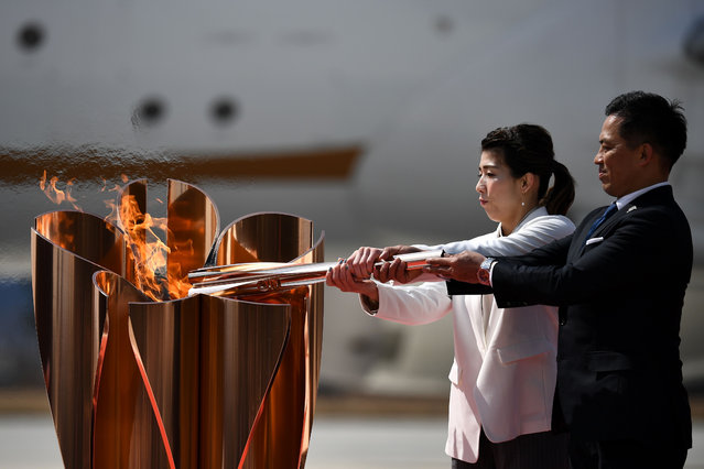Japanese three-time Olympic gold medallists Saori Yoshida (L) and Tadahiro Nomura (R) light a Tokyo 2020 Olympic cauldron with the Olympic flame, after transporting the flame from Greece, at the Japan Air Self-Defense Force Matsushima Base in Higashimatsushima, Miyagi prefecture on March 20, 2020. The Olympic flame arrives in Japan on March 20, with what should have been a joyous celebration dramatically downscaled as doubts grow over whether the Tokyo Games can go ahead during the coronavirus pandemic. (Photo by Philip Fong/AFP Photo)
