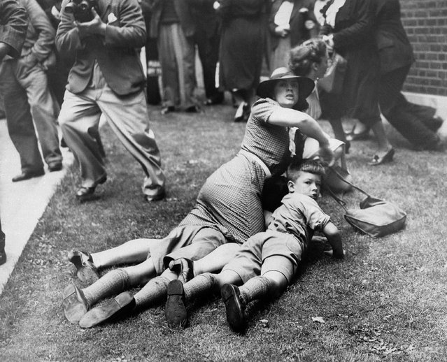 """Woman threw herself to the ground with her children and partly across one child to guard it from what she thought might be a bomb explosion. The incident occurred in London, August 28, 1939, when a """"Peace"""" agitator threw a number of rubber balls into a crowd of persons watching the arrival of ministers for a British Cabinet meeting. People fled in all directions believing that the balls were bombs. (Photo by AP Photo)"""