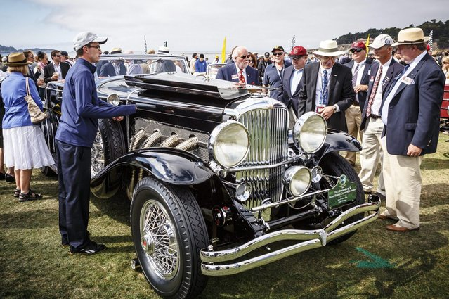 In this photo provided by Rolex, jury members inspect a 1933 Duesenberg SJ Brunn Riviera Convertible Sedan owned by John D. Groendyke at the Rolex Monterey Motorsports Reunion during Monterey's Classic Car Week, Sunday, August 17, 2014, in Carmel, Calif. (Photo by Tom O'Neal/AP Photo/Rolex)