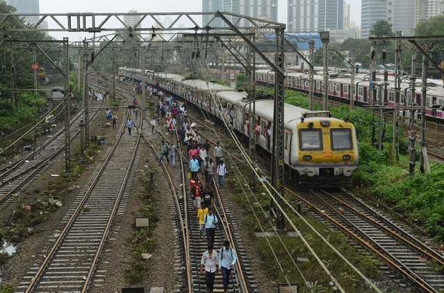 Indian commuters walk on railway tracks as train services slowly resume in Mumbai on August 30, 2017, after heavy rains brought major flooding to the coastal city. At least five people were killed as heavy monsoon rain deluged India's financial capital Mumbai, causing transport chaos and forcing schools and many offices to close on August 30. (Photo by Punit Paranjpe/AFP Photo)