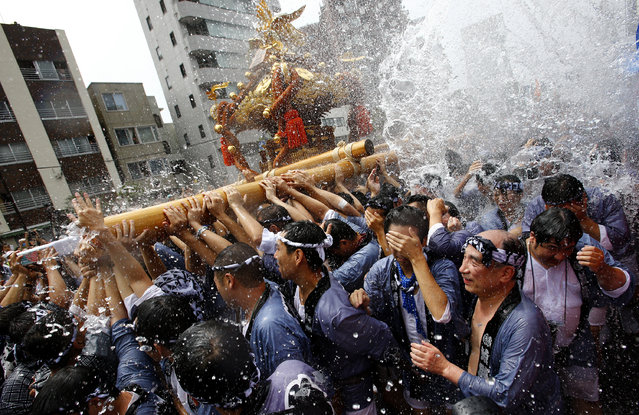 Festivalgoers, carrying portable shrine, are splashed with water during a summer festival of Tomioka Hachimangu Shrine in downtown Tokyo, Sunday, August 17, 2014. (Photo by Shizuo Kambayashi/AP Photo)