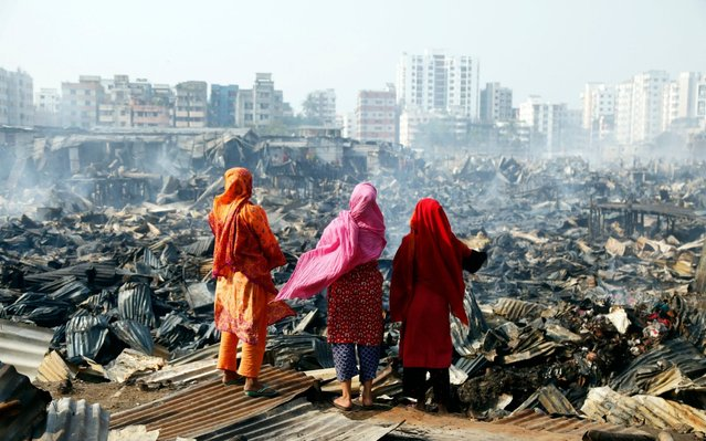 People affected by the disaster stand in ruins after a fire ripped through Rupnagar Slum in Dhaka, Bangladesh, 11 March 2020. Over 2,000 houses are wiped out in the fire and around 10,000 residents are affected, 20 firefighter units were deployed to contain the flames, according to reports. (Photo by Monirul Alam/EPA/EFE)