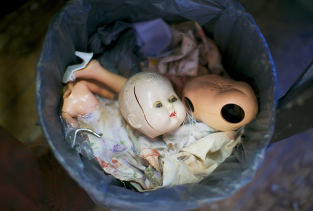 A trash can featuring discarded doll parts including a broken head, torso and limbs is pictured in the workshop of Sydney's Doll Hospital, July 12, 2014. Opened in 1913, Sydney's Doll Hospital has worked on millions of dolls, teddy bears and other toys. (Photo by Jason Reed/Reuters)