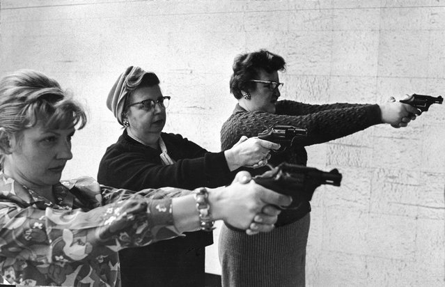 Two middle-aged women and one younger woman aim revolvers at a target in a indoor shooting range in Dearborn, Michigan, 1967 or 1968. (Photo by London Daily Express)
