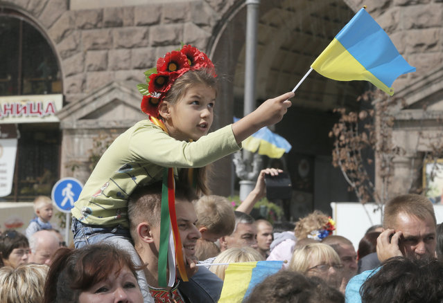 A Ukrainian girl waves the national flag sitting on her father's shoulders during celebration of Ukraine's 23rd Independence Day  in Kiev, Ukraine, Sunday, August 24, 2014. Ukraine leader announces $3 billion boost to defense spending to combat pro-Russian rebels. (Photo by Efrem Lukatsky/AP Photo)