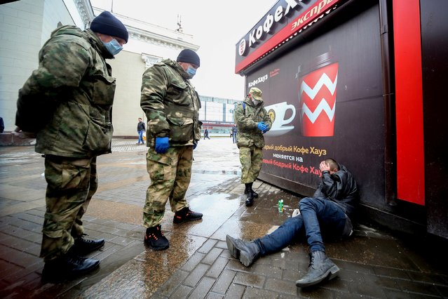 Cossacks wearing protective masks, used as a preventive measure against the coronavirus disease (COVID-19), surround a man lying on the pavement as they patrol streets and squares in Moscow, Russia on April 7, 2020. (Photo by Sergei Vedyashkin/Moscow News Agency/Handout via Reuters)