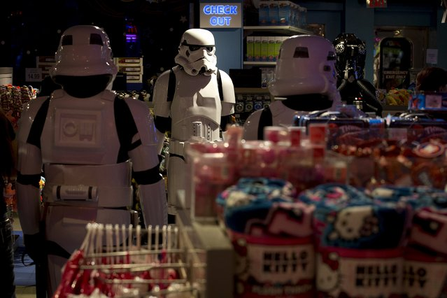 """People dressed up as characters from """"Star Wars"""" wait for people to walk in to purchase toys that went on sale at midnight in advance of the film """"Star Wars: The Force Awakens"""" in Times Square in the Manhattan borough of New York, September 4, 2015. (Photo by Carlo Allegri/Reuters)"""