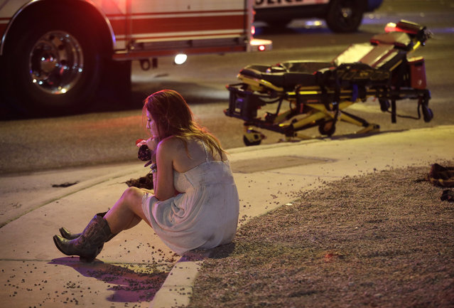 A woman sits on a curb at the scene of a shooting outside of a music festival along the Las Vegas Strip, Monday, October 2, 2017, in Las Vegas. Multiple victims were being transported to hospitals after a shooting late Sunday at a music festival on the Las Vegas Strip. (Photo by John Locher/AP Photo)