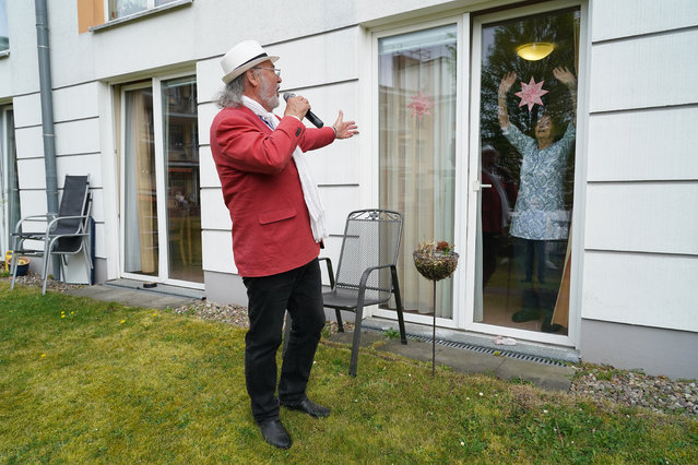 Resident Johanna Pfeiffer, 96, looks on from her room as singer Alf Weiss performs live at the Hermann Radtke Haus nursing home during the novel coronavirus crisis on April 29, 2020 in Berlin, Germany. The home, which has a total of 195 residents, has seen its share of Covid-19 infections, from which eight residents have died. Of the 12 remaining infected residents eight are recovering, according to the home's manager. Local performer Alf Weiss sang a mix of schmalzy hits for two hours outside in the courtyard of the home. Some residents emerged with walkers or electric wheelchairs to watch and listen, while others looked on from the windows of their rooms as a few nursing staff members danced. Many senior care facilities across Germany have been hit with Covid-19 infections. The Hermann Radtke Haus is part of the Diakonie Simeon gGmbH, a caregiving and social work organization of the Protestant Church. (Photo by Sean Gallup/Getty Images)