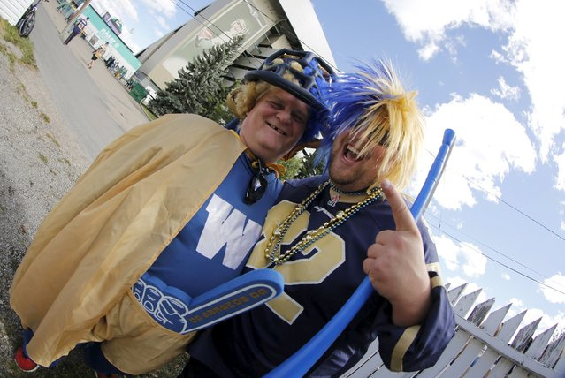Winnipeg Blue Bomber fans and brothers Doug (L) and Will Streilein pose before the Riders vs Winnipeg Blue Bombers CFL football game in Regina, Saskatchewan September 6, 2015. The brothers came out to Regina for the Labour Day Classic football game. (Photo by David Stobbe/Reuters)