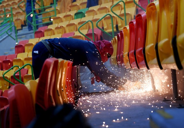 Fabio, a Brasilian worker, works on the stands of the Future Arena where the Olympic Handball competition will take place, at the Olympic Park in Rio de Janeiro on August 1, 2016, ahead of the Rio 2016 Olympic Games. (Photo by Roberto Schmidt/AFP Photo)