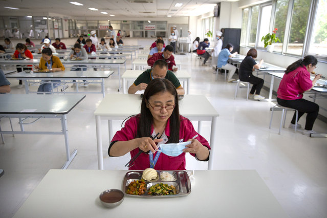 A worker removes her face mask as employees practice social distancing while they eat lunch at a staff cafeteria in a semiconductor production facility for Renesas Electronics during a government organized tour for journalists in Beijing, Thursday, May 14, 2020. China reported three new coronavirus cases Thursday while moving to reopen for business and schools. (Photo by Mark Schiefelbein/AP Photo)