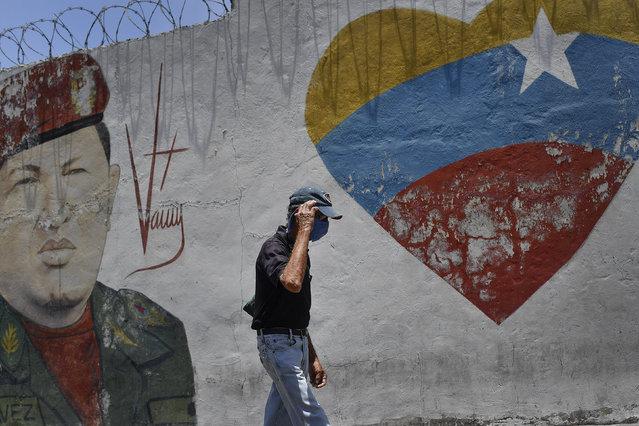 A man, wearing a protective face mask as a precaution against the new coronavirus, walks past a mural of the late Venezuelan President Hugo Chavez in the 23 de Enero neighborhood of Caracas, Venezuela, Saturday, April 11, 2020. (Photo by Matias Delacroix/AP Photo)