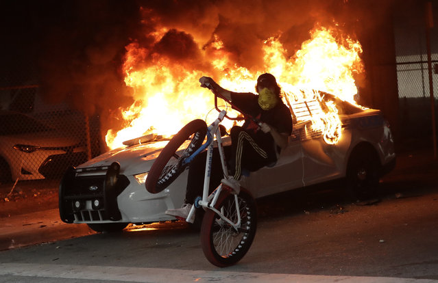 A protester on a bicycle rides past a burning police car during a demonstration next to the city of Miami Police Department, Saturday, May 30, 2020, downtown in Miami. Protests were held throughout the country over the death of George Floyd,  a black man who was killed in police custody in Minneapolis on May 25. (Photo by Wilfredo Lee/AP Photo)