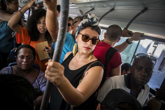 In this June 12, 2016 photo, Cuban American Fontaine Capel, center, travels on a regular bus line in Havana, Cuba. Capel was brought to the island by CubaOne, a new program inspired by the reestablishment of diplomatic and business ties between the U.S. and Cuba. (Photo by Ramon Espinosa/AP Photo)