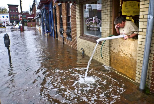 Sveinn Storm pumps water out of his flooded Storm Bros. Ice Cream Factory store in downtown Annapolis, Maryland. (Photo by Blake Sell/Associated Press)