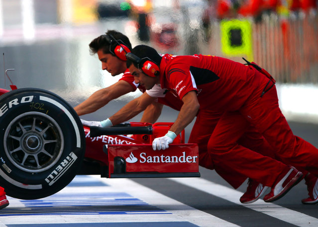 Ferrari Formula One mechanics push the car of Kimi Raikkonen of Finland during the first free practice session of the Russian F1 Grand Prix in the Sochi Autodrom circuit October 10, 2014. (Photo by Laszlo Balogh/Reuters)