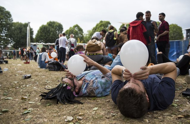 Revellers inhale from a balloon at the Notting Hill Carnival on August 28, 2016 in London, England. (Photo by Jack Taylor/Getty Images)