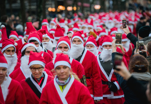 """Charity runners dressed as Father Christmas participate in a """"Santa Run"""" charity fun run in Stockholm on December 10, 2017. Hundreds of participants dressed in Santa suits and wearing white beards ran through the streets of the old town in Stockholm in an all charity run. (Photo by Jonathan Nackstrand/AFP Photo)"""
