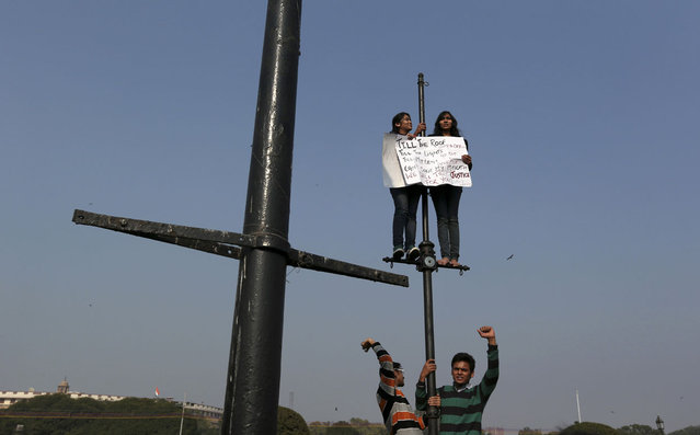 Demonstrators shout slogans and carry a placard while standing on lamp posts during a protest rally near the presidential palace in New Delhi, on December 22, 2012. (Photo by Ahmad Masood/Reuters)