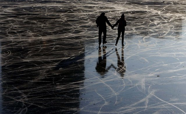 A young couple enjoys a cold afternoon at a frozen pond in Prague, Czech Republic. (Photo by Petr David Josek/Associated Press)