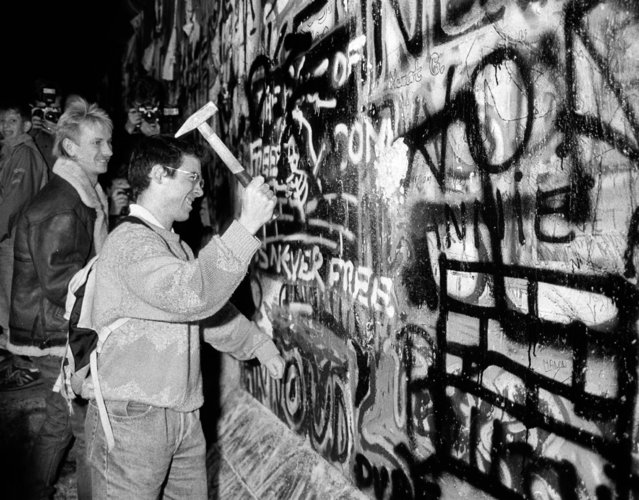 A man hammers a section of the Berlin Wall near the Brandenburg Gate after the opening of the East German border was announced, November 9, 1989. (Photo by Reuters)