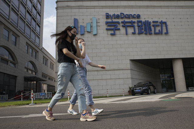 Women wearing masks to prevent the spread of the coronavirus chat as they pass by the ByteDance headquarters in Beijing, China on Friday, August 7, 2020. President Donald Trump on Thursday ordered a sweeping but unspecified ban on dealings with the Chinese owners of consumer apps TikTok and WeChat, although it remains unclear if he has the legal authority to actually ban the apps from the U.S. TikTok is owned by Chinese company ByteDance. (Photo by Ng Han Guan/AP Photo)