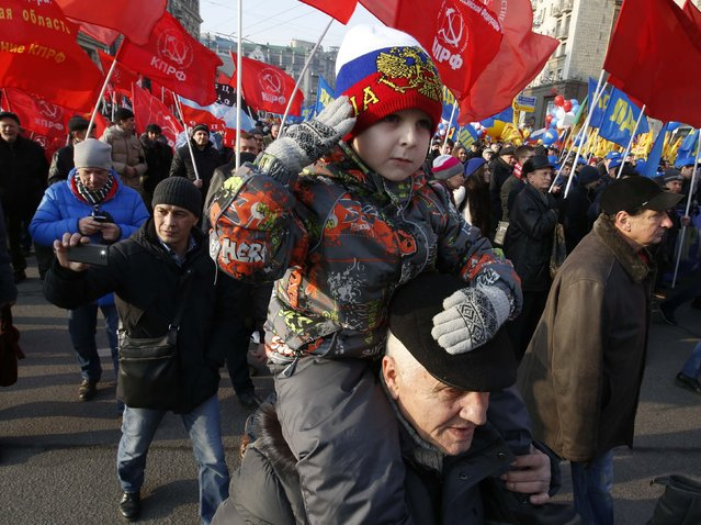 A boy salutes as he sits on his grandfather's shoulders while Russian communists attend a demonstration on National Unity Day in Moscow November 4, 2014. (Photo by Sergei Karpukhin/Reuters)