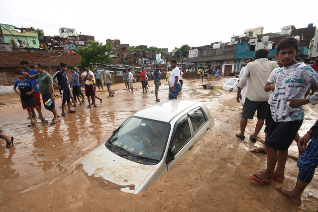 People stand next to a car partially covered in mud due to flooding after a heavy monsoon rainfall in Jaipur on August 14, 2020. (Photo by Rohit Jain Paras/AFP Photo)