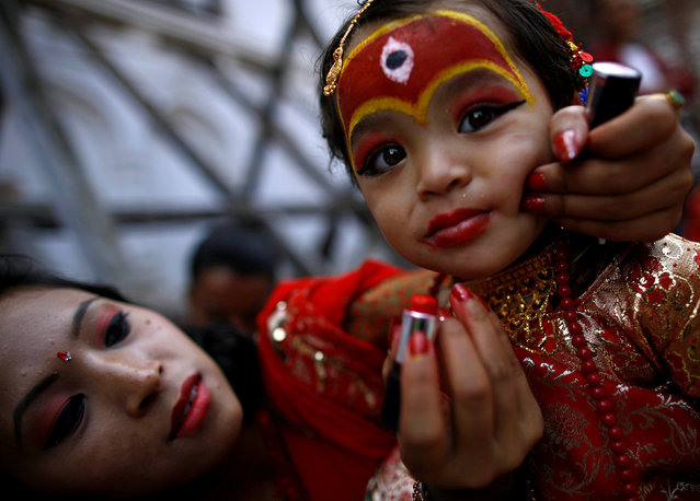 A woman applies makeup to the face of a young girl dressed as the Living Goddess Kumari during the Kumari Puja festival in Kathmandu, Nepal September 14, 2016. (Photo by Navesh Chitrakar/Reuters)