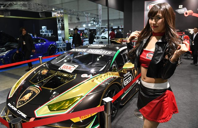 A model poses beside a Lamborghini Huracan race car at the Tokyo Auto Salon at the Makuhari Messe in Chiba on January 12, 2018. (Photo by Toshifumi Kitamura/AFP Photo)