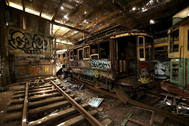 In this October 22, 2014 photo, old tramcars and trolley buses sit abandoned and wrecked in the Loftus Tram Shed in Sydney. Trams became a key part of life in Sydney after the network was installed in 1879, with 1,600 cars in service during the height of its popularity. The service was eventually shut down in 1961. (Photo by Rob Griffith/AP Photo)