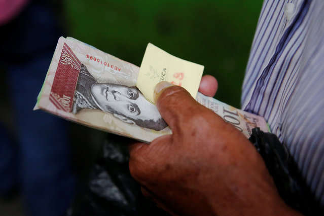 A man holds Venezuelan bolivar notes as he queues trying to buy basic food during a special inspection of Venezuelan soldiers to a municipal market in Caracas, Venezuela July 15, 2016. (Photo by Carlos Garcia Rawlins/Reuters)