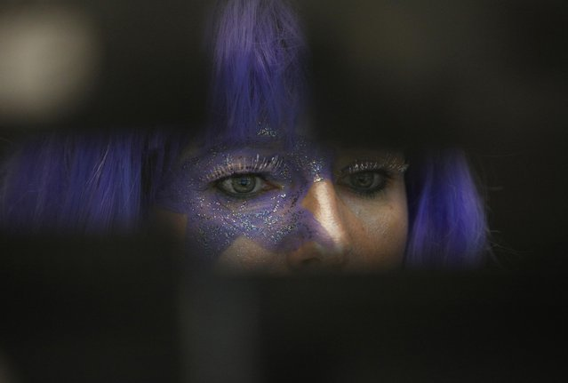 A share trader dressed in a carnival costume checks share prices at the stock exchange on Shrove Tuesday in Frankfurt February 12, 2013. Frankfurt's bourse traders follow a long tradition by wearing carnival costumes on Shrove Tuesday. (Photo by Lisi Niesner/Reuters)