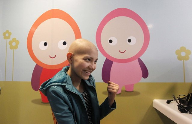 Isidora Serrano, 14, who lost her hair due to chemotherapy to treat her bone cancer, reacts upon hearing from her doctor the positive results of a blood test during her daily treatment in the cancer ward of the Luis Calvo Mackenna Hospital in Santiago, October 20, 2014. (Photo by Rodrigo Garrido/Reuters)