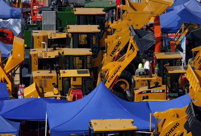 An exhibitor (R) chats with a visitor amidst construction vehicles on display at the China Import and Export Fair, also known as Canton Fair, in the southern Chinese city of Guangzhou October 15, 2015. (Photo by Bobby Yip/Reuters)