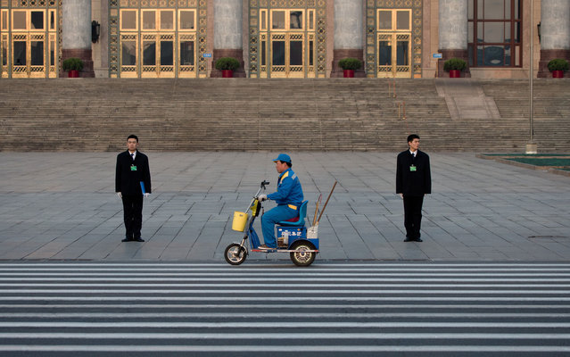 A street cleaner on an electronic bike passes by People's Liberation Army soldiers dressed as ushers while they stand guard in front of the Great Hall of the People before the opening session of the National People's Congress in Beijing Tuesday, March 5, 2013. In a rare move, China declined to reveal its defense budget request for 2013. Every year, the country announces its defense spending plan for the upcoming year at a press conference before the opening of an annual session of the National People's Congress, China's parliament. (Photo by Andy Wong/AP Photo)
