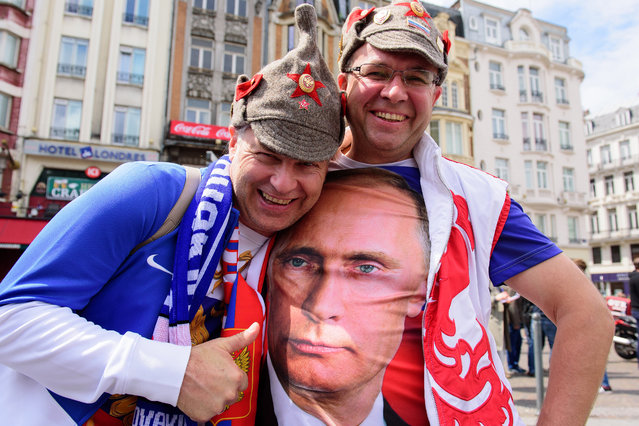 A Russia supporter poses with a fellow fan wearing a t-shirt featuring Russian President Vladimir Putin as they walk in central Lille on June 15, 2016 ahead of the Euro 2016 group B football match between Russia and Slovakia. (Photo by Leon Neal/AFP Photo)