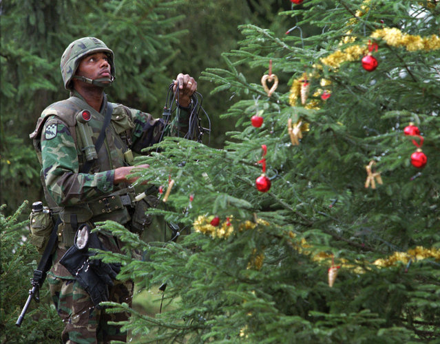 U.S. Army Sgt. Eugene Davis from  Philadelphia, Pa. hangs lights on a Christmas tree Saturday, December 23, 1995 at the Tuzla Airbase in Bosnia. (Photo by Ruth Fremson/AP Photo)