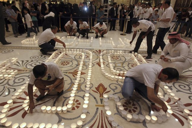People light candles to mark Earth Hour at the Ritz Carlton in Riyadh, March 23, 2013. Earth Hour, when everyone around the world is asked to turn off the lights for an hour from 8.30pm local time, is meant as a show of support for tougher actions to combat climate change. (Photo by Reuters/Stringer)