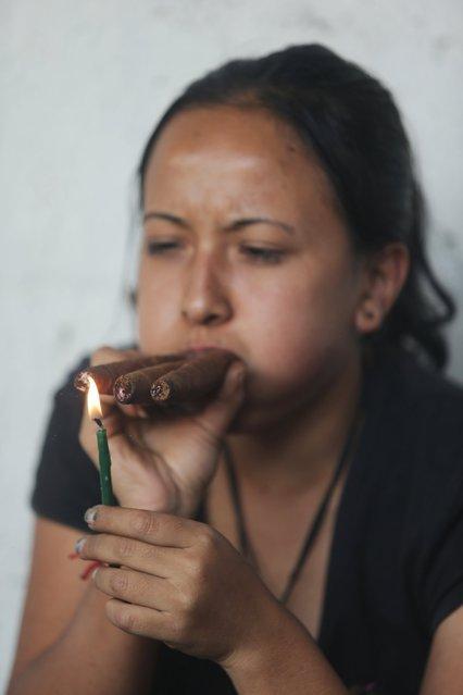 A woman smokes cigars outside the church of San Simon in Iztapa, Chimaltenango, Guatemala, October 28, 2015. (Photo by Jorge Dan Lopez/Reuters)