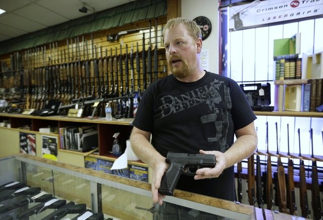 Eric Grabowski holds a hand gun, very similar to the gun used by alleged gunman Wade Michael Page, in The Shooter Shop, where Page purchased the weapon, in West Allis, Wisconsin, August 7, 2012. The gun used in the crime was the crime was identical, only it had a shorter barrel. The semiautomatic handgun used in the deadly attack on a Wisconsin Sikh temple is the same type used in other recent U.S. mass shootings, including one at a theater in Colorado, and the attack on a congresswoman in Arizona, gun experts said. (Photo by John Gress/Reuters)